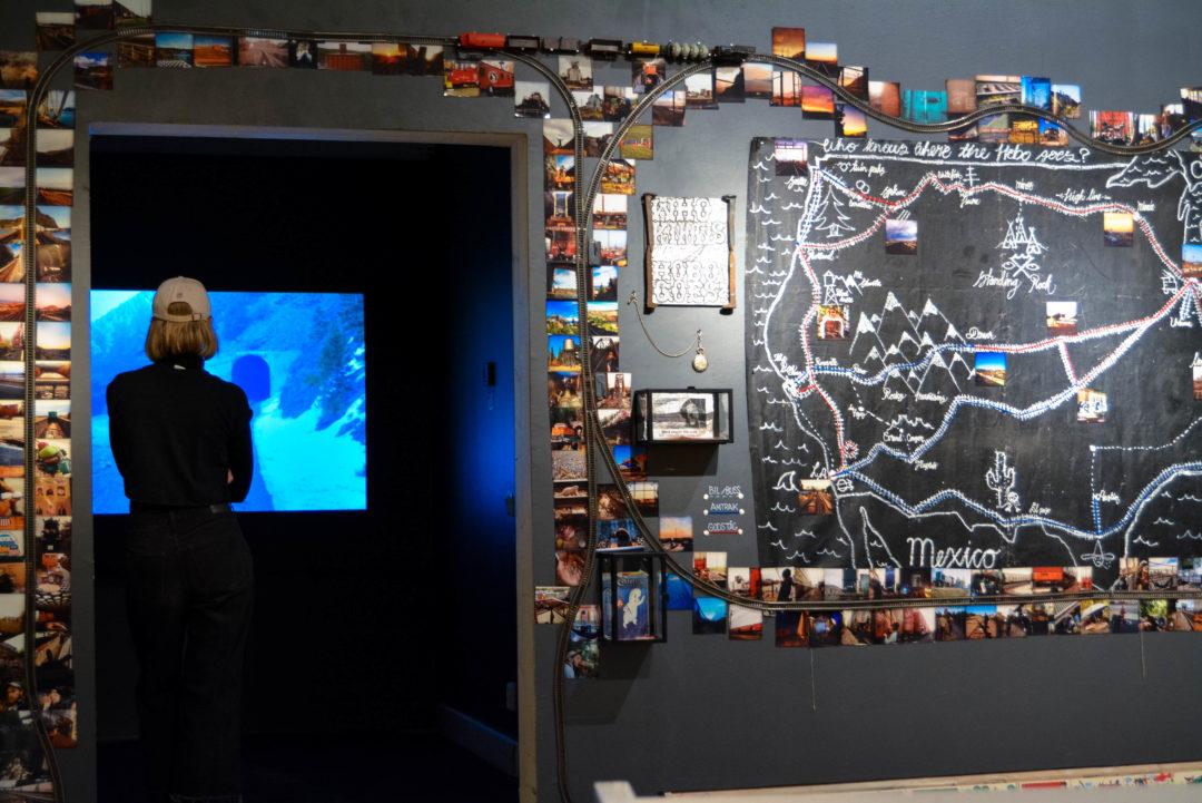 Foto från utställningen ett kollage med fotografier biljetter och annat plockigt på väggen
