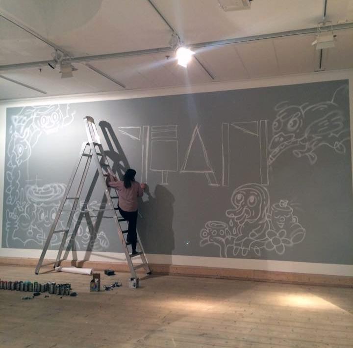 En kvinna står på en trappa och målar en muralmålning